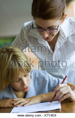 Junior high student watching at teacher corrects classwork - Stock Photo