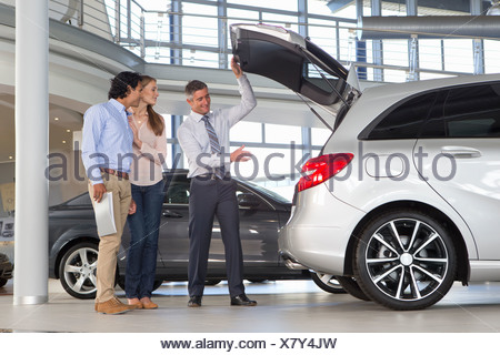 Salesman and couple looking into hatchback of car in car dealership showroom - Stock Photo