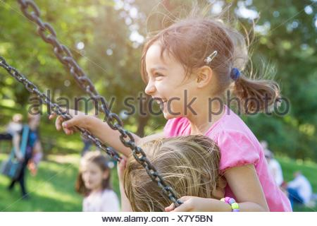 Two young girls swinging together on park swing - Stock Photo