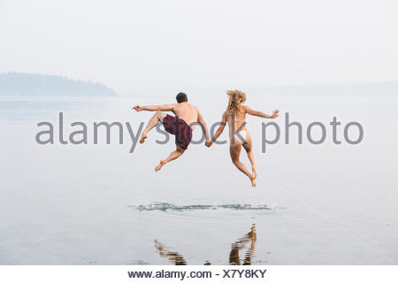 Young couple on beach, holding hands, jumping, mid air, rear view - Stock Photo