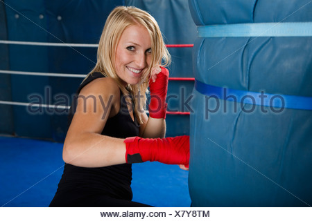 Boxer training with punching bag - Stock Photo