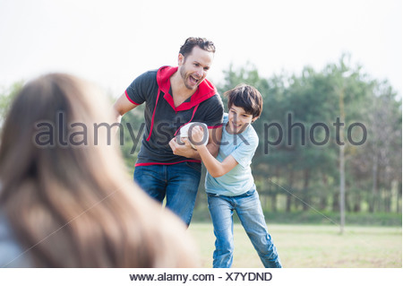 Father and son practicing rugby tackle in park - Stock Photo