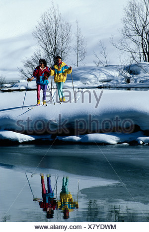 two cross-country skier standing at a brook. - Stock Photo