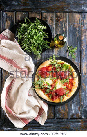 Whole homemade pizza with cheese and bresaola, served on black plate with fresh arugula, olive oil and kitchen towel over old wooden plank background. - Stock Photo