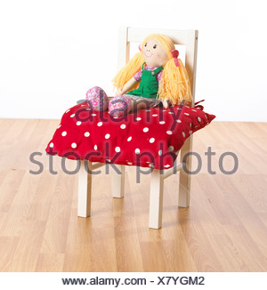 Rag doll sitting on red polka dot cushion on childs chair - Stock Photo