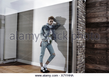 Young woman leaning against wall looking out of window - Stock Photo