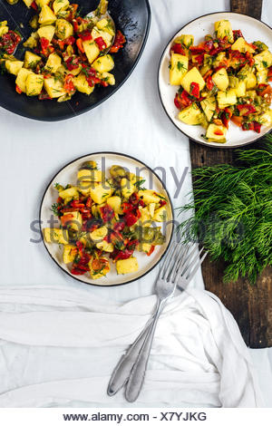 Vegan potato salad with roasted peppers served in a black bowl and on two smaller white plates photographed from top view. Fresh dill and garlic on a  - Stock Photo