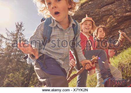 Three children exploring forest - Stock Photo