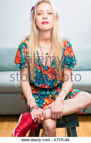 Young woman sitting in floral patterned dress, portrait - Stock Photo