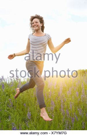 Woman leaping in tall grass - Stock Photo