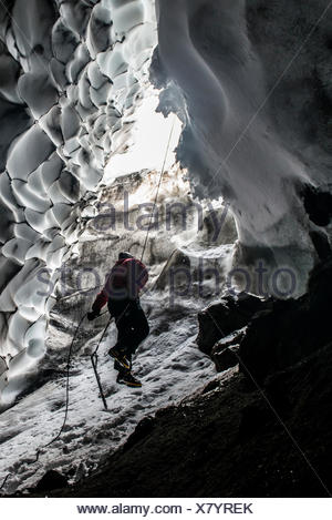 A scientist ascends a rope to exit a steam cave. - Stock Photo