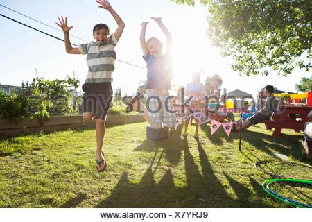 Portrait playful boys jumping for joy sunny park - Stock Photo