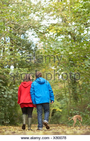 Young couple walking in woods with whippet - Stock Photo
