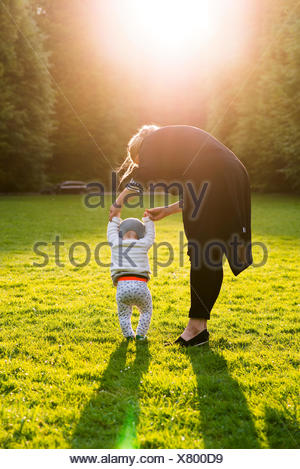 Sweden, Skane, Malmo, Mother walking with son (18-23 months) in park - Stock Photo