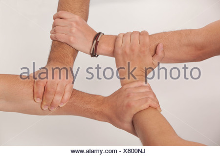 Hands linked holding teamwork four boys teenagers - Stock Photo