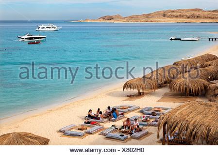 People at beach on pillow seats, beach, parasols, lagoon, swimmers, people, ships, Beach Mahmya, beach, Giftun Island, Hurghada - Stock Photo