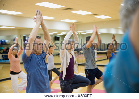 Group practicing tree pose in yoga class - Stock Photo