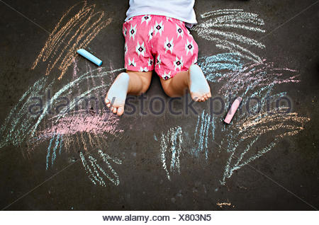 Overhead view of girl lying on ground drawing with chalk - Stock Photo