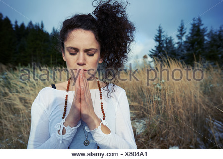 Mid adult woman meditating in forest - Stock Photo