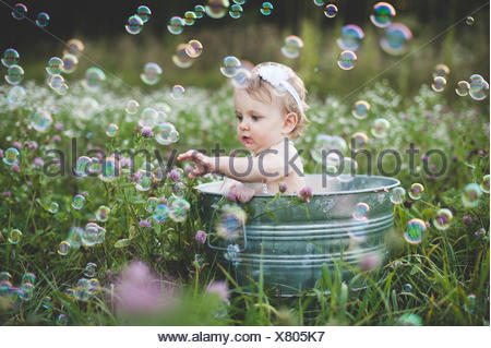 Baby girl in tin bathtub in meadow reaching for floating bubbles - Stock Photo