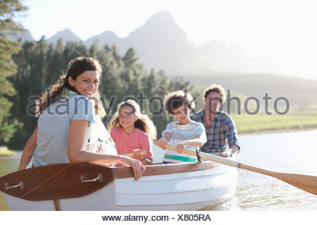 Family in rowboat on lake - Stock Photo
