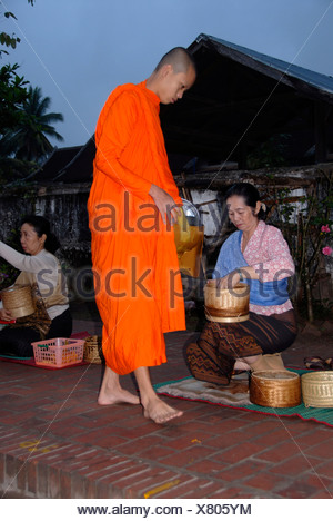Buddhist monk with begging bowl receiving rice in the morning, Luang Prabang, Laos, Southeast Asia - Stock Photo