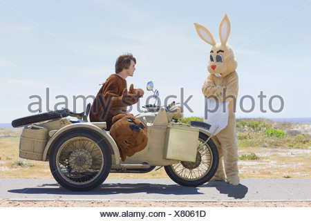 Disguised couple on motorbike - Stock Photo