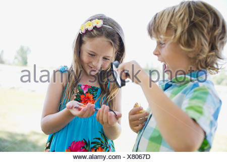 Siblings examining insects with magnifying glass - Stock Photo