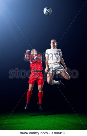 Two female soccer players heading ball - Stock Photo