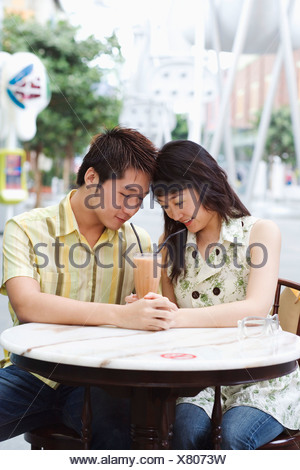 Close-up of a young couple sitting in a cafeteria - Stock Photo