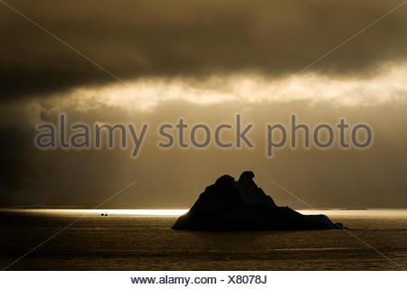 Sunlight shining through a hole in the clouds, silhouette of an iceberg at the front, Errera Channel, Arctowski Peninsula - Stock Photo