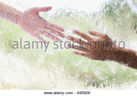 Two hands reaching out behind glass - Stock Photo