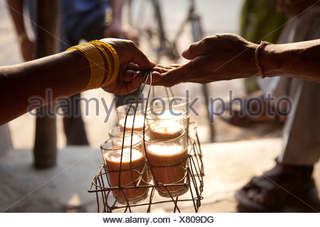 Close-up of female's hand passing tray of chai to man with people in background - Stock Photo