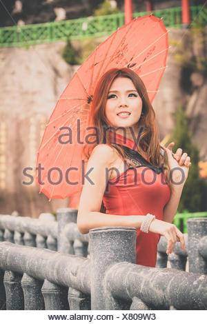 Portrait of young woman with umbrella - Stock Photo