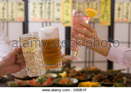 Three People Toasting with Each Other With Various Drinks at Izakaya - Stock Photo