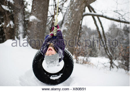 Girl upside down on tire swing in snow - Stock Photo