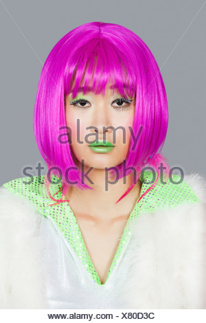 Portrait young woman wearing pink wig over - Stock Photo