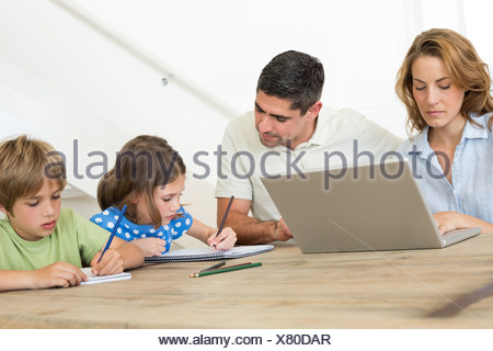 Mother using laptop while father assisting children in coloring - Stock Photo