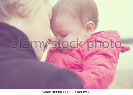 Portrait of mother and baby daughter (6-11 months) touching foreheads - Stock Photo