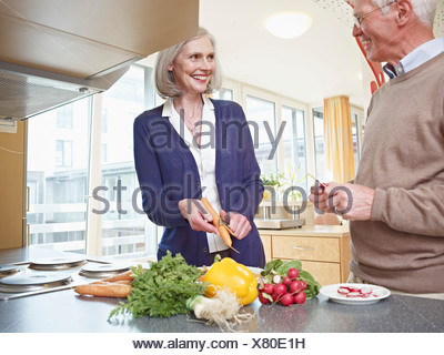 Germany, Cologne, Senior couple cutting vegetables, smiling - Stock Photo