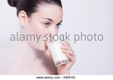 Portrait of beautiful young woman drinking glass of milk - Stock Photo