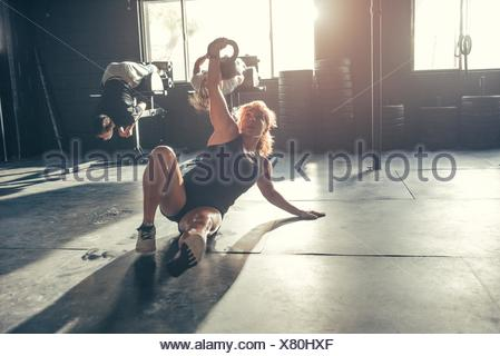 Woman training with kettlebell in gym - Stock Photo