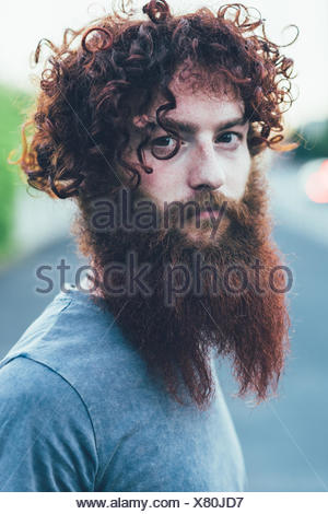 Portrait of curly haired, bearded young male hipster - Stock Photo