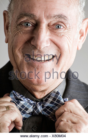 Senior man putting on bow tie - Stock Photo