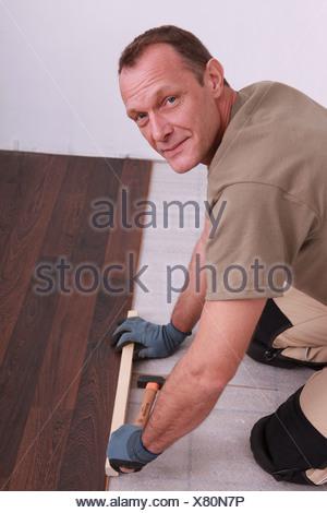 Fitting laminate flooring - Stock Photo