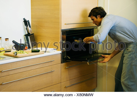 Man putting pan into oven - Stock Photo