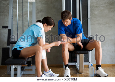 Two friends listening to music in a gym - Stock Photo