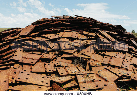 A large pile of rusty plates, used for railroad construction. Discarded or piled up for recycling. - Stock Photo