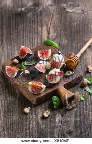 Fresh sliced figs with ricotta cheese, basil leaves, hazelnut and honey from honey dipper on small wood cutting board over dark - Stock Photo