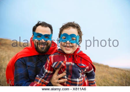 Portrait of father and son in superhero capes - Stock Photo